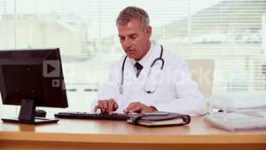 Smiling doctor using his computer