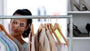 Beautiful woman picking clothes on a clothes rail