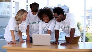 Group of volunteers using laptop together