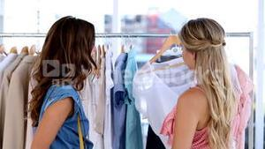Two cheerful friends doing shopping together