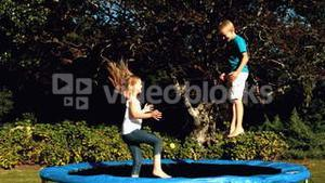Siblings playing together on a trampoline