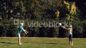 Brother throwing a football to a sister in a park