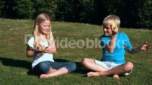 Siblings sat in a park playing with tennis balls