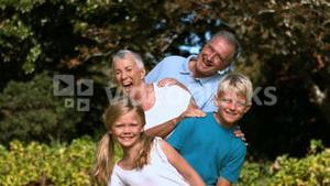 Cheerful multigeneration family posing in a park