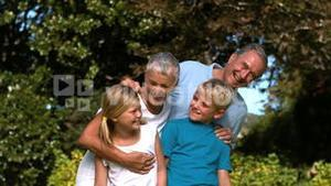 Cheerful multigeneration family embracing in a park