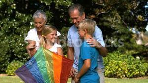 Little girl holding a kite with her grandparents