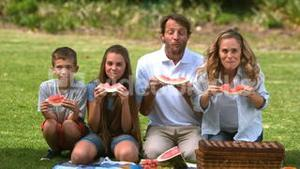 Happy family eating a watermelon while having a picnic