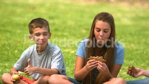 Siblings eating a sandwich together