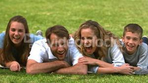 Family lying on the grass and looking at camera