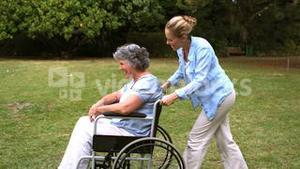 Young woman pushing her mother in wheelchair