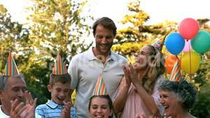 Happy family celebrating a birthday and clapping hands