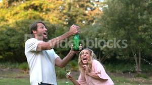 Happy man shaking a bottle of champagne and kissing his wife