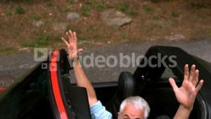 Man raising up his hands in a car