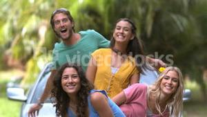 Friends jumping on side and smiling