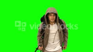 Man with a coat and a hiking stick running on green screen