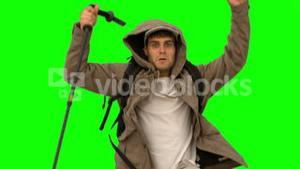 Man with a hiking stick jumping on green screen