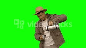 Man pouring coffee from a vacuum flask on green screen
