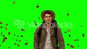 Man walking under leaves falling on green screen