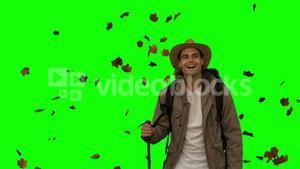 Cheerful man standing under leaves falling on green screen