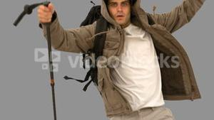 Man with a hiking stick running on grey screen