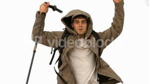 Man with a hiking stick jumping on white screen