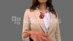 Businesswoman throwing a die on grey screen