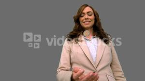 Businesswoman throwing a coin in the air on grey screen