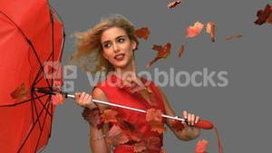 Glamour woman holding a broken umbrella on grey screen
