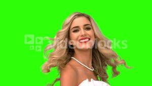 Pretty woman tossing her hair on green screen
