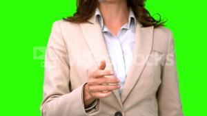 Pretty businesswoman throwing a coin on green screen