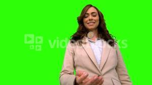 Businesswoman throwing a coin in the air on green screen