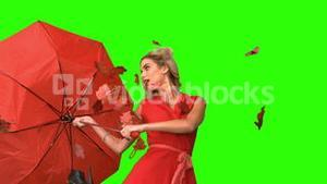 Pretty glamour woman holding a broken umbrella on green screen