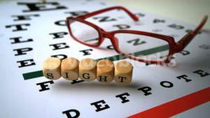 Dice spelling out sight falling onto eye test next to glasses