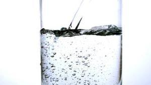 Water being poured into a glass over white background