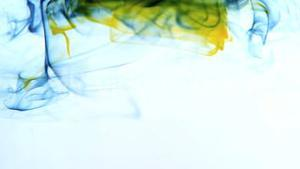 Yellow and blue ink swirling in water on white background