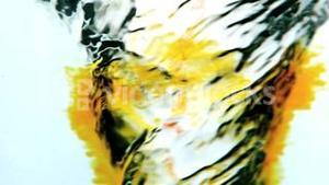 Yellow ink swirling into water whirlpool on white background