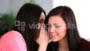 Attractive woman telling her friend a secret