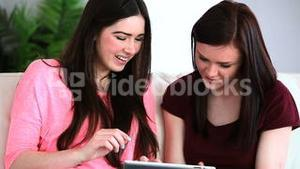 Two friends using a digital tablet
