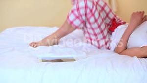 Woman sitting on bed picking up her phone