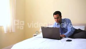 Cheerful businessman typing on his notebook in bed