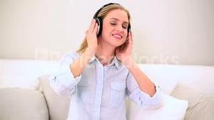 Smiling blonde woman listening music and dancing on sofa