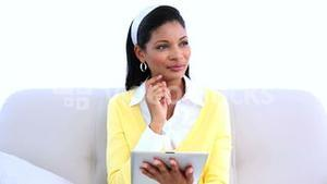 Woman sitting on sofa using tablet pc