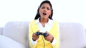 Concentrated woman playing video games on sofa