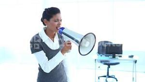 Furious businesswoman screaming in a megaphone