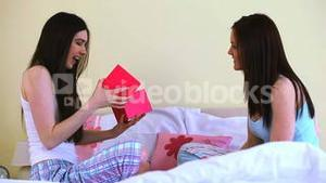 Woman offering gift to her friend