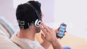 Handsome man listening to music on his smartphone