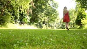 Beautiful teen walking away on the grass on a sunny day