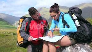 Couple using map and compass to find the way on a rock