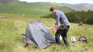 Couple setting up their tent for the night