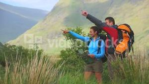Active couple hiking together with map and pointing